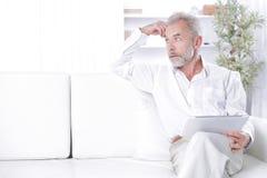 Hög affärsman med digitalt minnestavlasammanträde på soffan royaltyfri foto