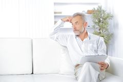 Hög affärsman med digitalt minnestavlasammanträde på soffan arkivfoto
