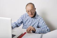 Hög affärsman som använder bärbara datorn, medan läsa mappen på kontorsskrivbordet Royaltyfria Bilder