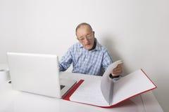 Hög affärsman som använder bärbara datorn, medan läsa mappen på kontorsskrivbordet Arkivfoton
