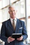 Hög affärsman som arbetar på minnestavladatoren Royaltyfri Fotografi