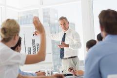 Hög affärsman som framlägger stångdiagrammet till hans kollegor som frågar frågor Arkivbild