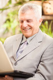 Hög affärsman som hemma arbetar Royaltyfria Bilder