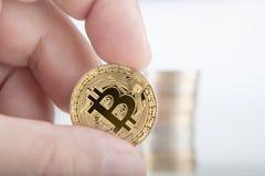 Hög affärsman som rymmer en guld- Bitcoin på bitcoinsbackgrou fotografering för bildbyråer
