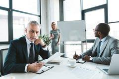 hög affärsman som ser kameran, medan ha konversation med kollegor fotografering för bildbyråer