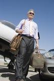 Hög affärsman Walking At Airfield Royaltyfria Bilder