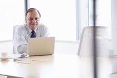 Hög affärsman Working On Laptop på styrelsetabellen Arkivfoto