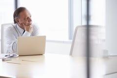 Hög affärsman Working On Laptop på styrelsetabellen Royaltyfri Fotografi