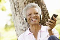 Hög afrikansk amerikankvinna, i att lyssna till spelaren MP3 royaltyfri fotografi