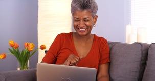 Hög afrikansk kvinna som har gyckel med bärbara datorn royaltyfria bilder