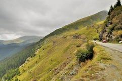 Hög alpin väg med rörande bilar Arkivfoton