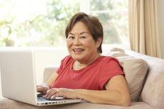 hög användande kvinna för home bärbar dator royaltyfria bilder
