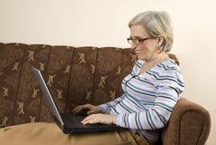hög användande kvinna för lycklig bärbar dator Arkivbilder