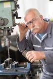 Hög arbetare i flygplanfabrik genom att använda borrandemaskinen Royaltyfri Fotografi