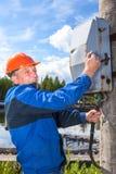 Hög arbetare med elektrisk chock som vänder därefter maktströmbrytaren Arkivfoton