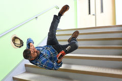 Hög arbetare som faller på trappa Royaltyfri Foto