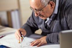 Hög arkitekt som i regeringsställning arbetar på konstruktionsritning Royaltyfri Fotografi