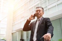 Hög asiatisk affärsman på en telefon royaltyfri fotografi
