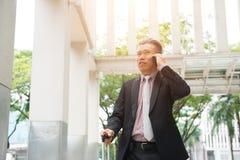 Hög asiatisk affärsman på en telefon arkivbild
