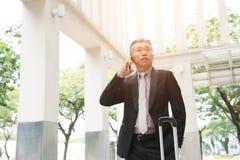 Hög asiatisk affärsman på en telefon royaltyfri bild