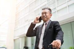 Hög asiatisk affärsman på en telefon royaltyfria bilder