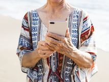 Hög asiatisk kvinna som använder en telefon på stranden royaltyfria foton