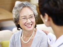 Hög asiatisk kvinna som talar till en doktor arkivbild