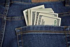Hög av amerikansk pengarUSA-valuta, USD i bakfickan av jeans med guling som syr som ett symbol av svarta pengar Royaltyfri Bild