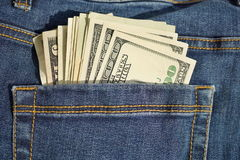 Hög av amerikansk pengarUSA-valuta, USD i bakfickan av jeans med guling som syr som ett symbol av svarta pengar Royaltyfri Fotografi