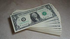 Hög av Amerikas förenta stater $1 kontanta räkningar arkivfoton