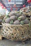 Hög av ananors i stor korg Royaltyfri Fotografi
