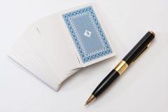 Hög av att spela kort med den svarta blyertspennan och anteckningsboken Arkivfoton