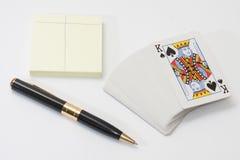 Hög av att spela kort och den svarta blyertspennan med anteckningsboken Arkivbild