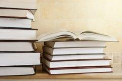 Hög av böcker med den öppna boken på marmorhylla Bokhylla med pil Royaltyfria Bilder