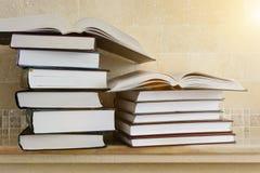 Hög av böcker med den öppna boken på marmorhylla Bokhylla med pil Royaltyfri Foto