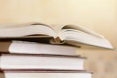 Hög av böcker med den öppna boken på marmorhylla Bokhylla med pil Royaltyfria Foton