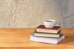 Hög av böcker med kaffekoppen överst på bakgrund fotografering för bildbyråer