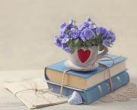 Hög av blåa böcker och blommor Arkivfoto