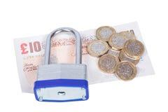 Hög av brittisk valuta med en hänglås överst arkivfoton