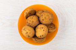 Hög av bruna kakor i orange bunke på trätabellen Royaltyfri Bild