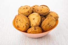 Hög av bruna kakor i orange glass bunke på tabellen Fotografering för Bildbyråer