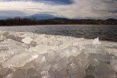 Hög av bruten is along lakeshore i Colorado Royaltyfria Foton