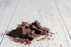 Hög av choklad på wood textur Arkivbilder