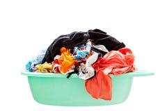 Hög av den smutsiga tvätterit i en tvagningkorg på vit bakgrund Royaltyfri Fotografi