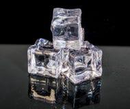 Hög av en liten vit och genomskinliga iskuber som isoleras på den svarta bakgrunden arkivbild