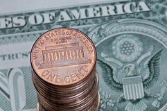 Hög av en USA-cent mynt på en dollarräkning Royaltyfri Foto