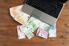 Hög av europengar med bärbara datorn Arkivbilder