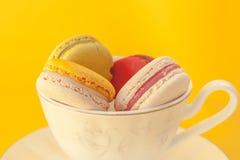 Hög av färgrika macarons som staplas upp i den vita klassiska koppen arkivbild