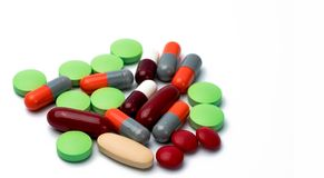 Hög av färgrika minnestavlor och kapselpreventivpillerar som isoleras på vit bakgrund Växelverkan för drog, för vitamin, för till royaltyfria bilder