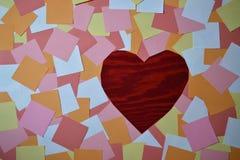 Hög av färgrika notepads med röd trähjärta arkivbild
